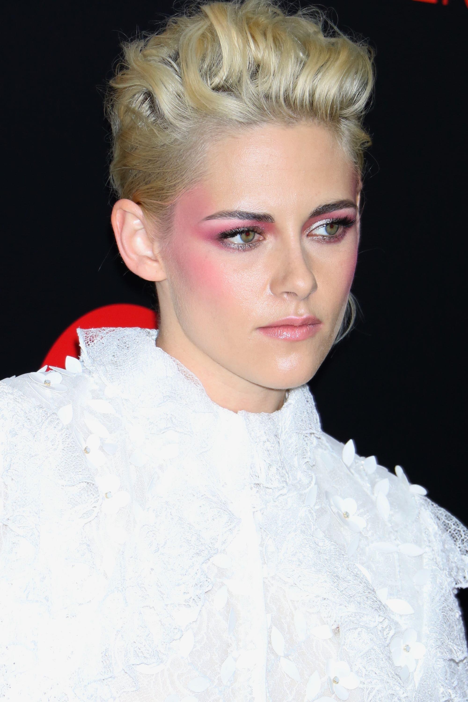 Mujer rubia de raices oscuras, lleva el cabello corto peinado hacia atrás