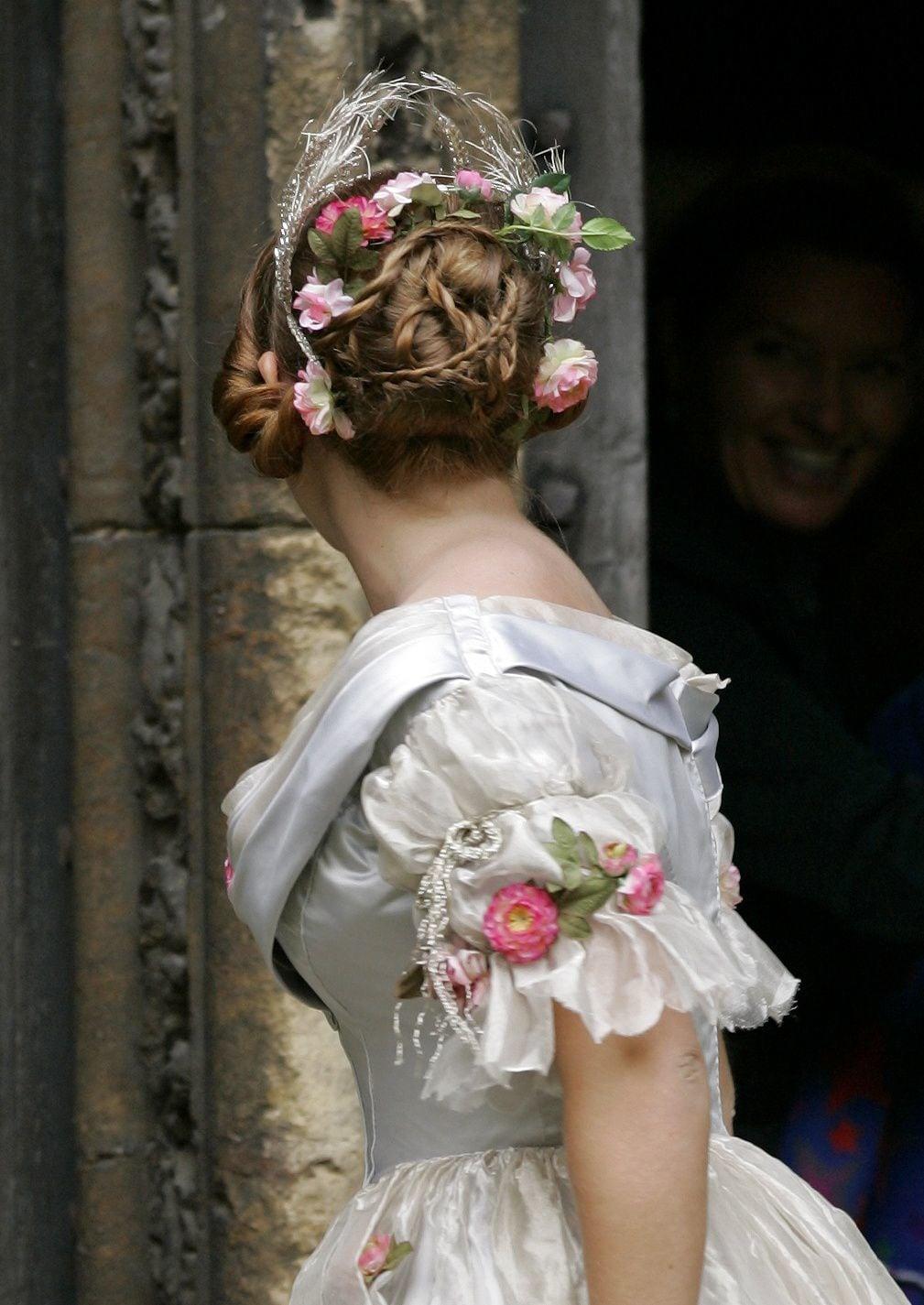 Mujer rubia con cabello atado con varias trenzas y rosas en el medio