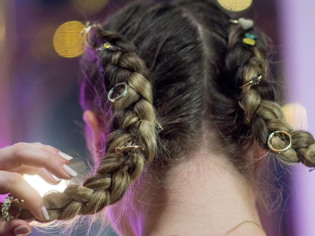 Vista de atrás de cabello castaño claro peinado con dos trenzas en la que se incrustan anillos y otros accesorios de bijou