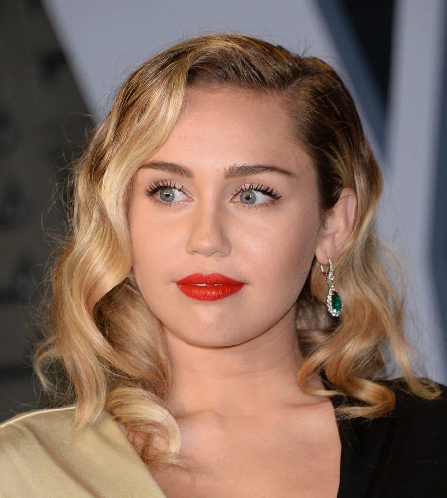 Miley Cyrus con cabello rubio por los hombros peinado con ondas y raya a un costado con un semi jopo