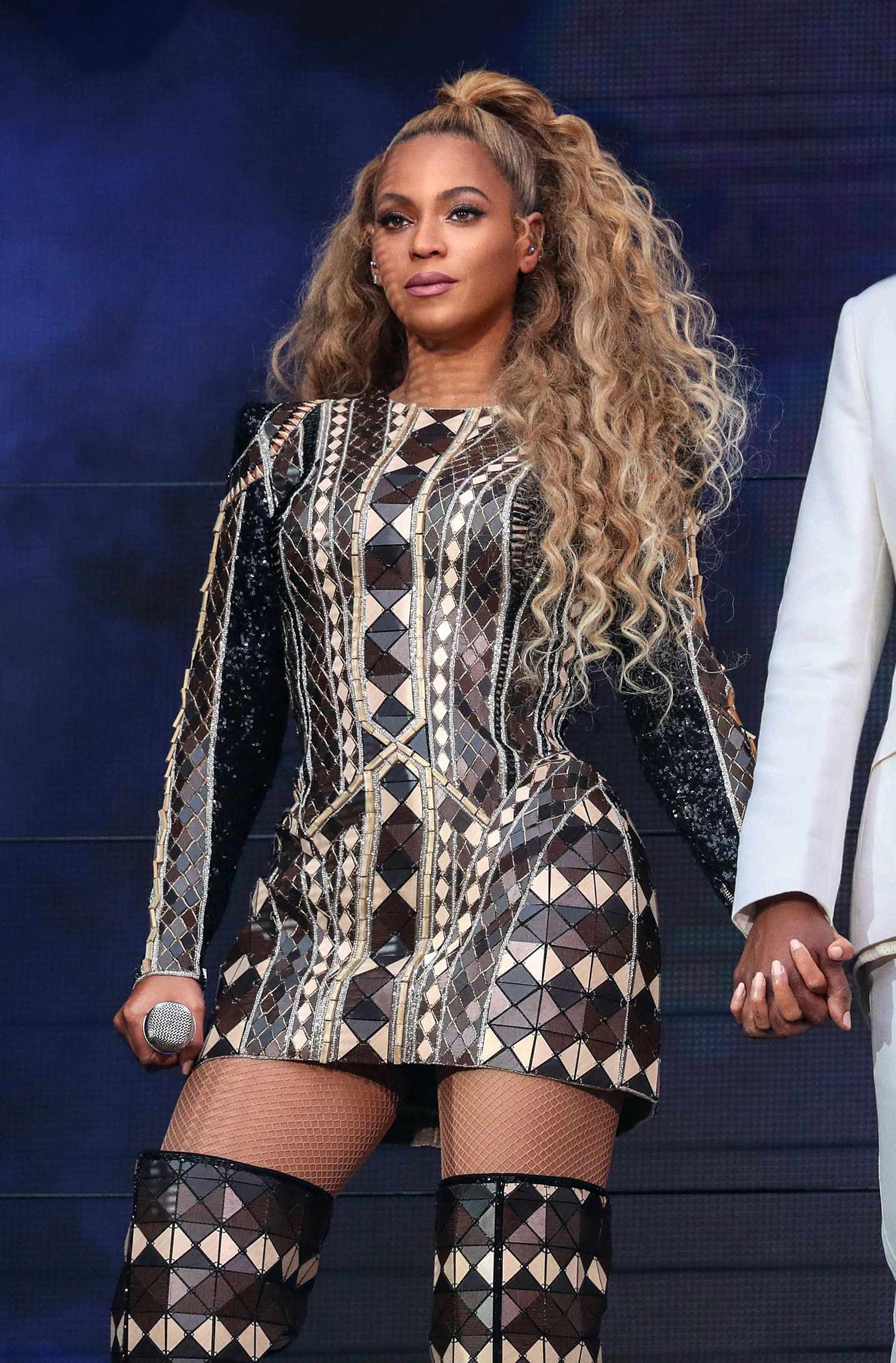 Beyonce con cabello super largo, rizado, rubio. Las raices son lacias y de ahí se abre una gran coleta