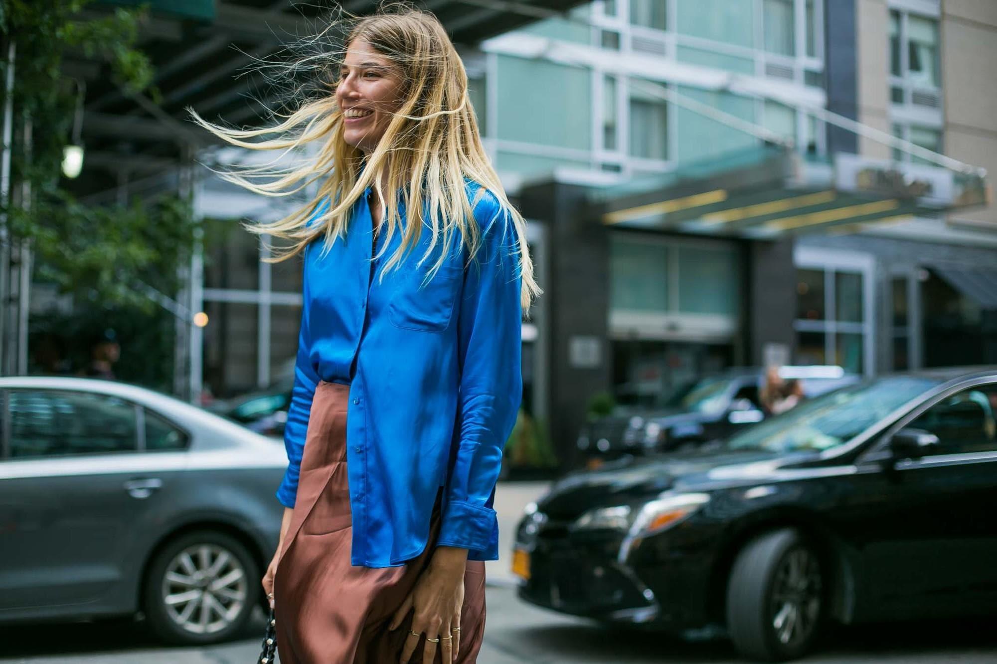 Mujer de melena rubia lacia, con el cabello agitado por el viento