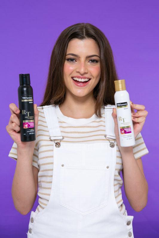chica con dos frascos de shampoo y acondicionador