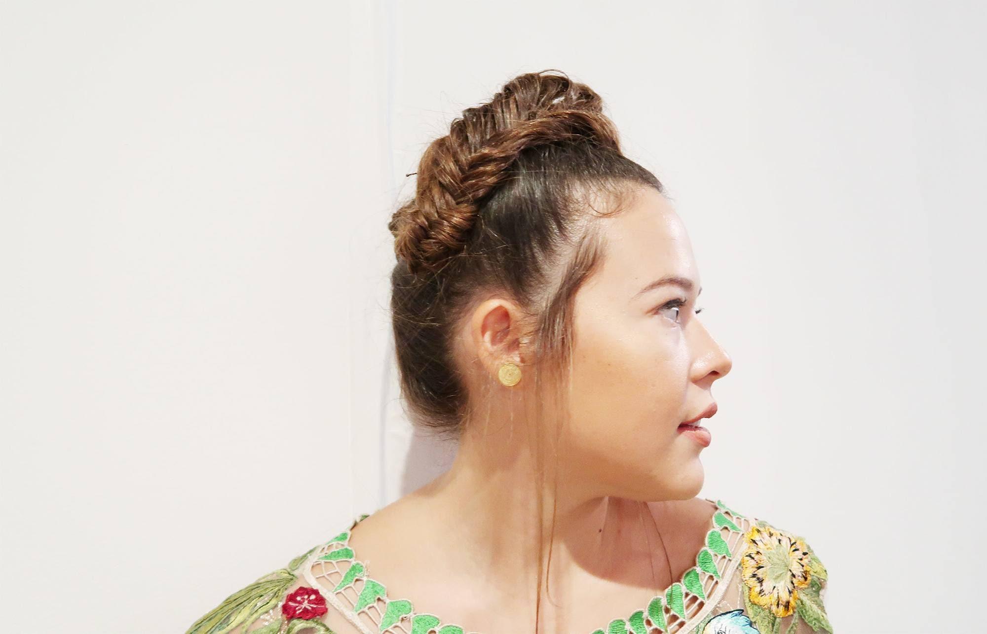Vista de perfil de mujer castaña con cabello sujeto en una trenza que le zurca el pelo