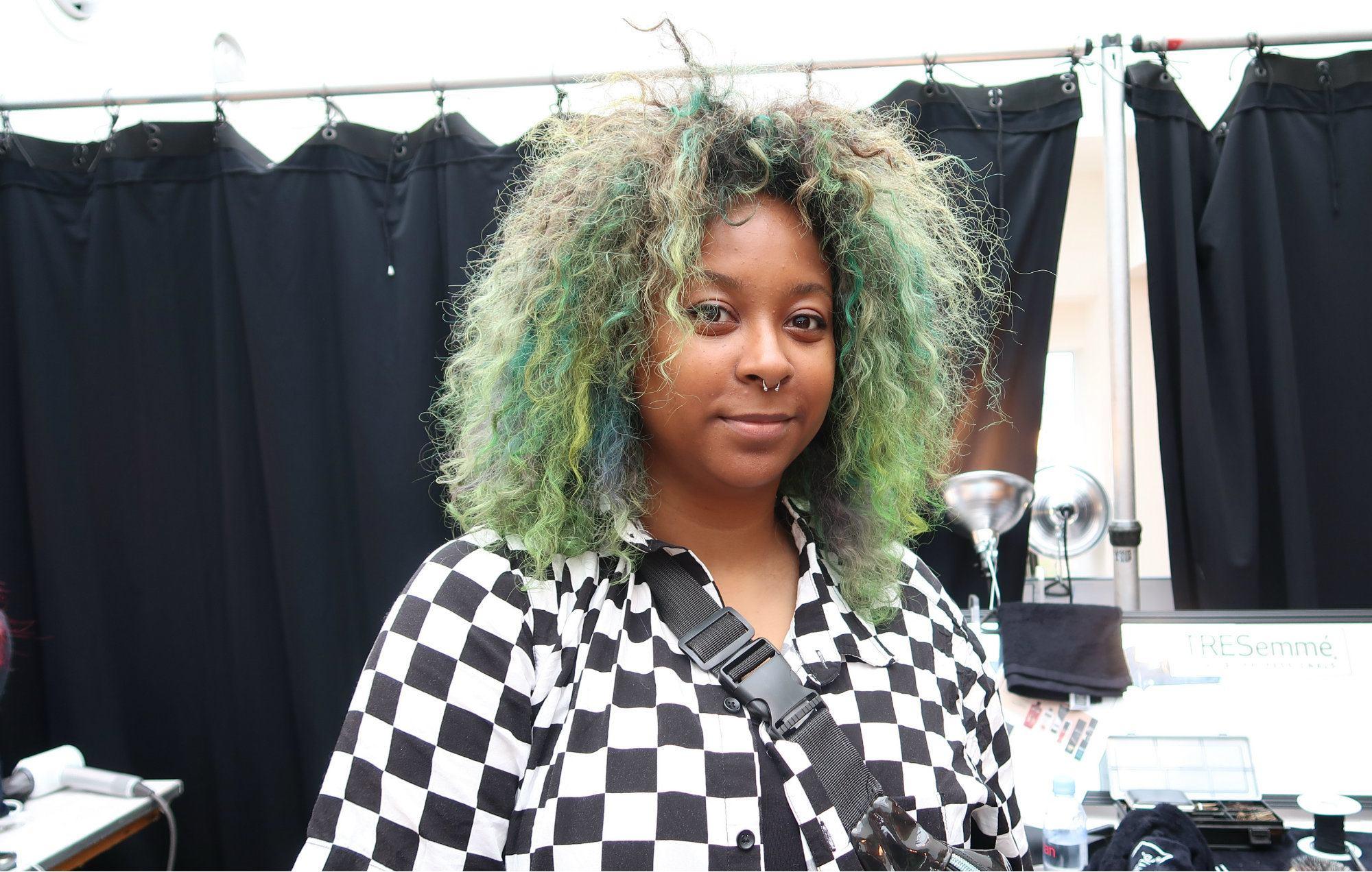 Mujer de cabello bien rizado, teñido de verde con raya al medio. Corte sobre los hombros