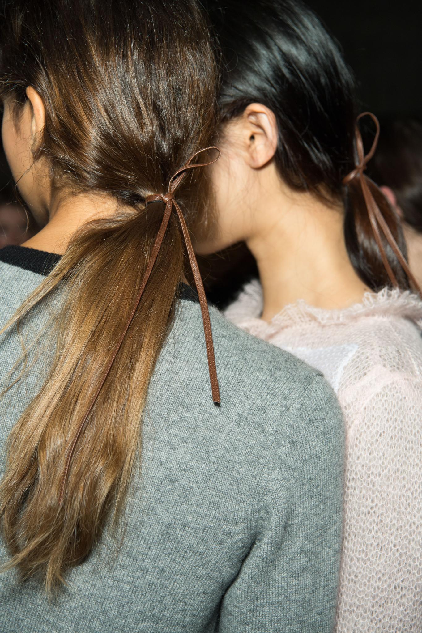 Vista de atrás de mujer castaña con coleta baja