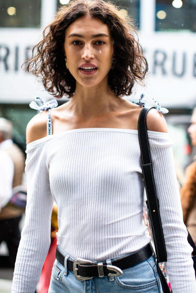 Mujer con corte por encima de los hombros, lleva el cabello rizado, castaño y con raya al medio