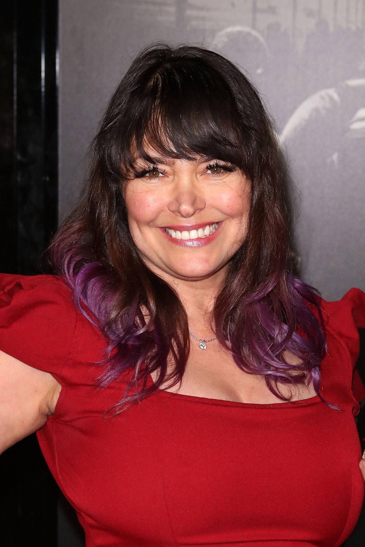 Mujer de melena por debajo de los hombros, castaña oscura con puntas violetas. El pelo es lacio, con movimiento y flequillo