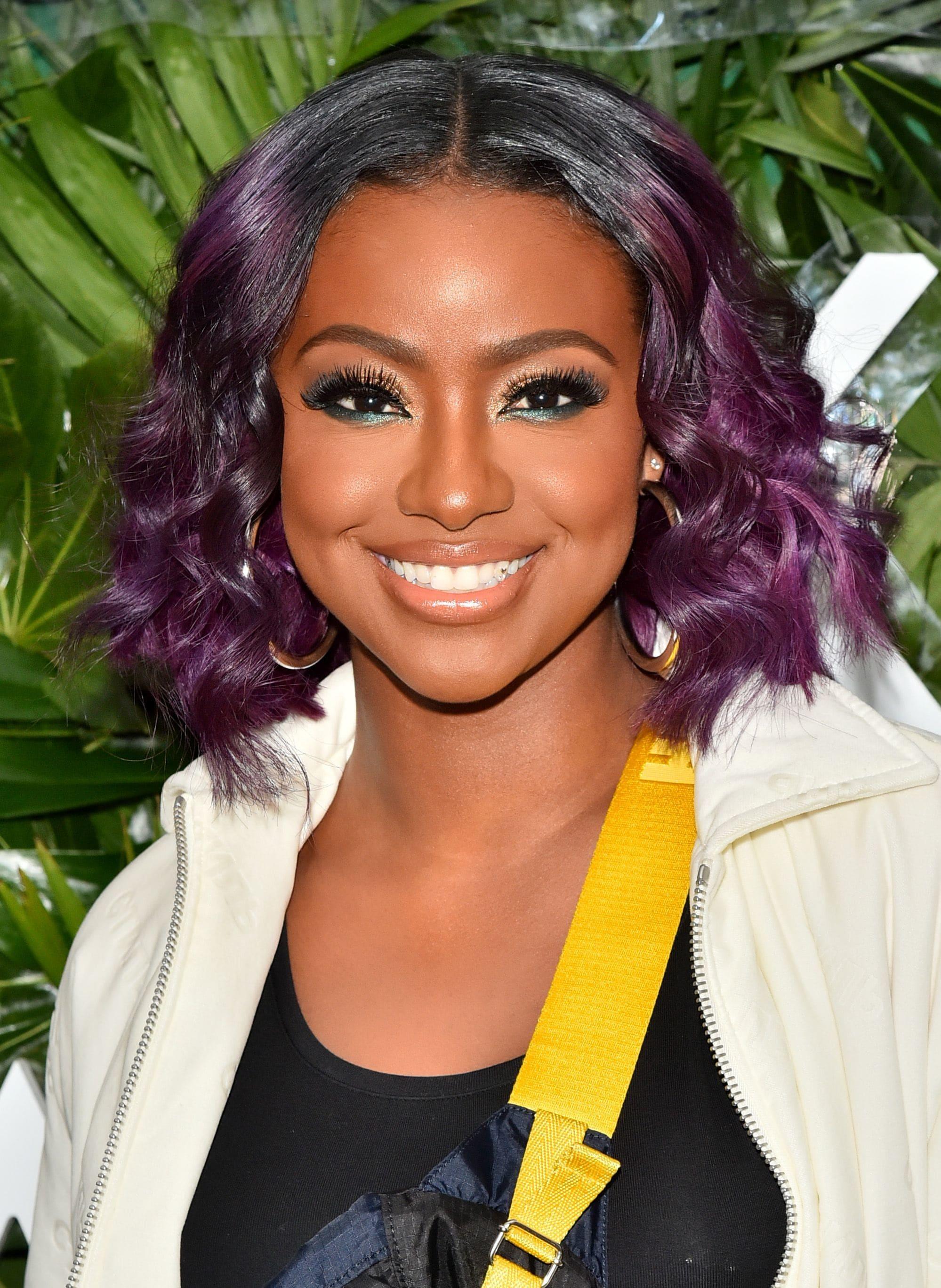 Mujer morena con cabello ondulado teñido de violeta a la altura de las orejas con raya al medio