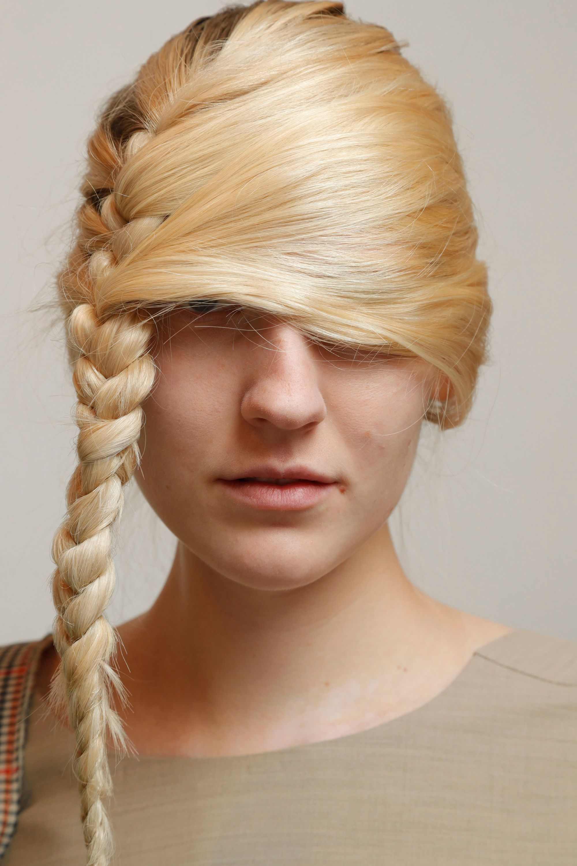 Mujer rubia de cabello lacio peinado con una trenza que sale de un extremo y va al otro, por lo que le cubre el rostro hasta debajo de los ojos