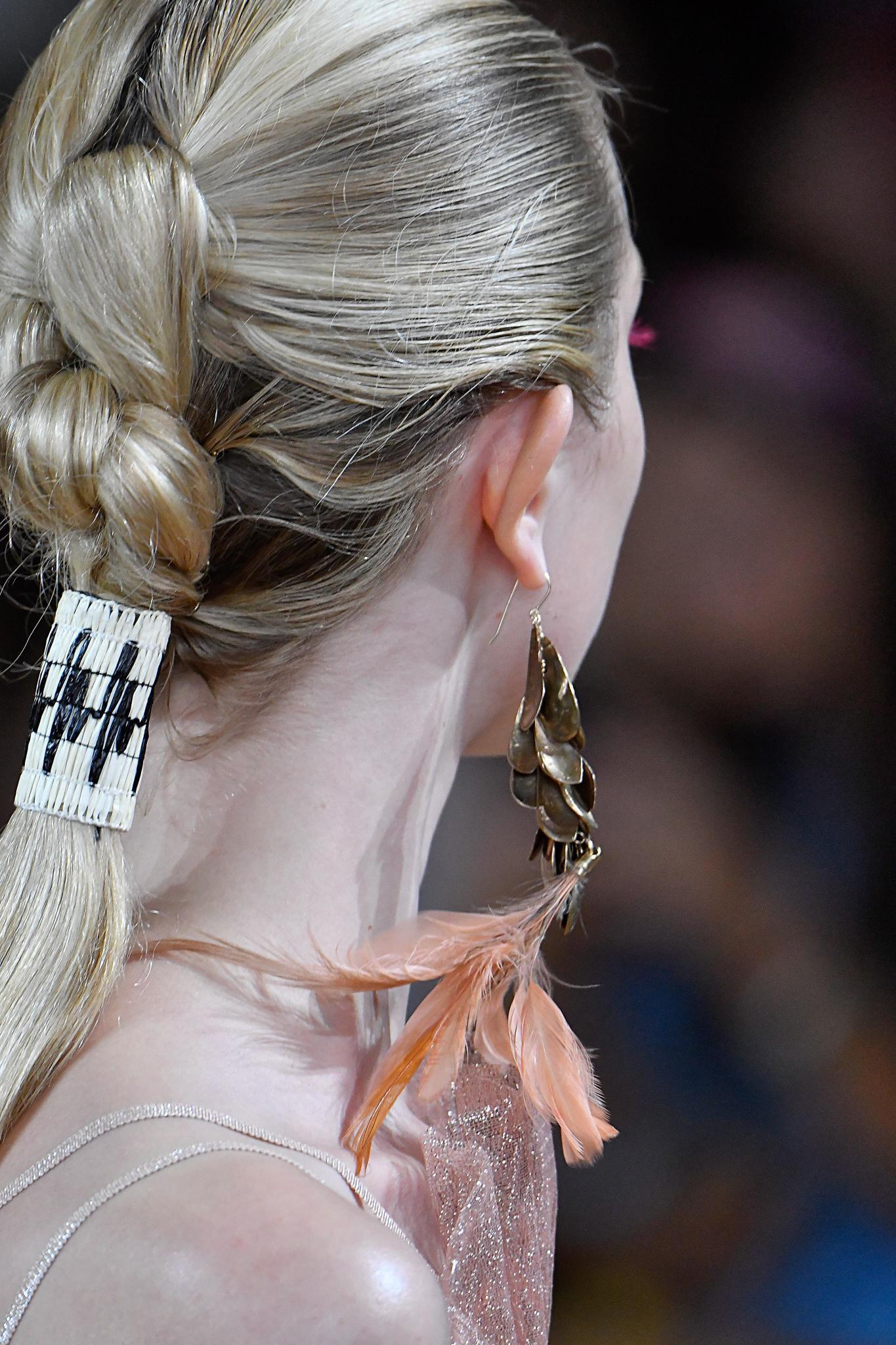 Vista de perfil de mujer rubia peinada con trenza que termina en una coleta