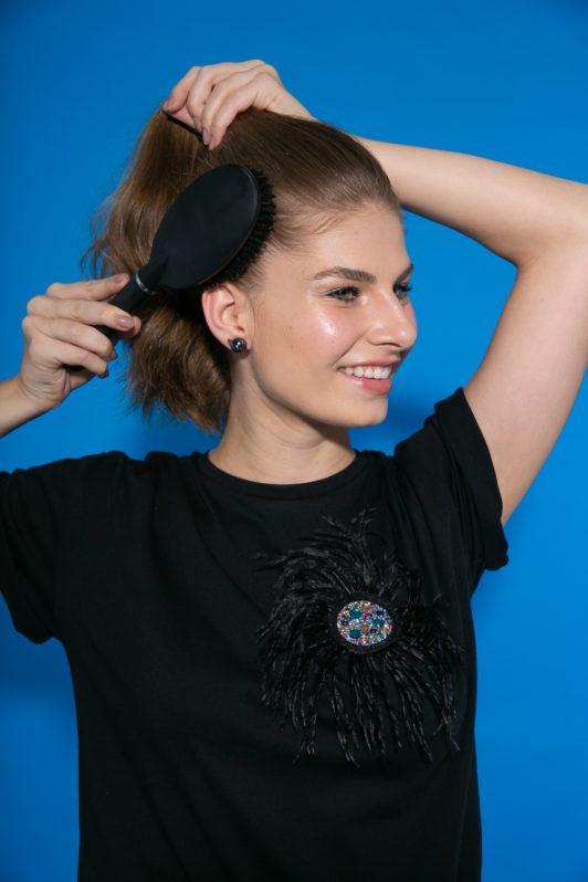 Chica de perfil peinándose el pelo con cepillo