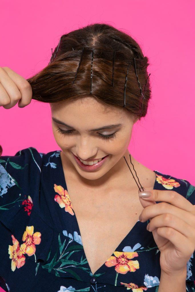 Chica castaña oscura colocando horquillas en el pelo