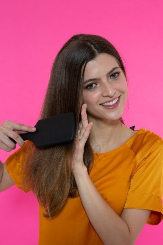 Chica castaña peinando el pelo lacio