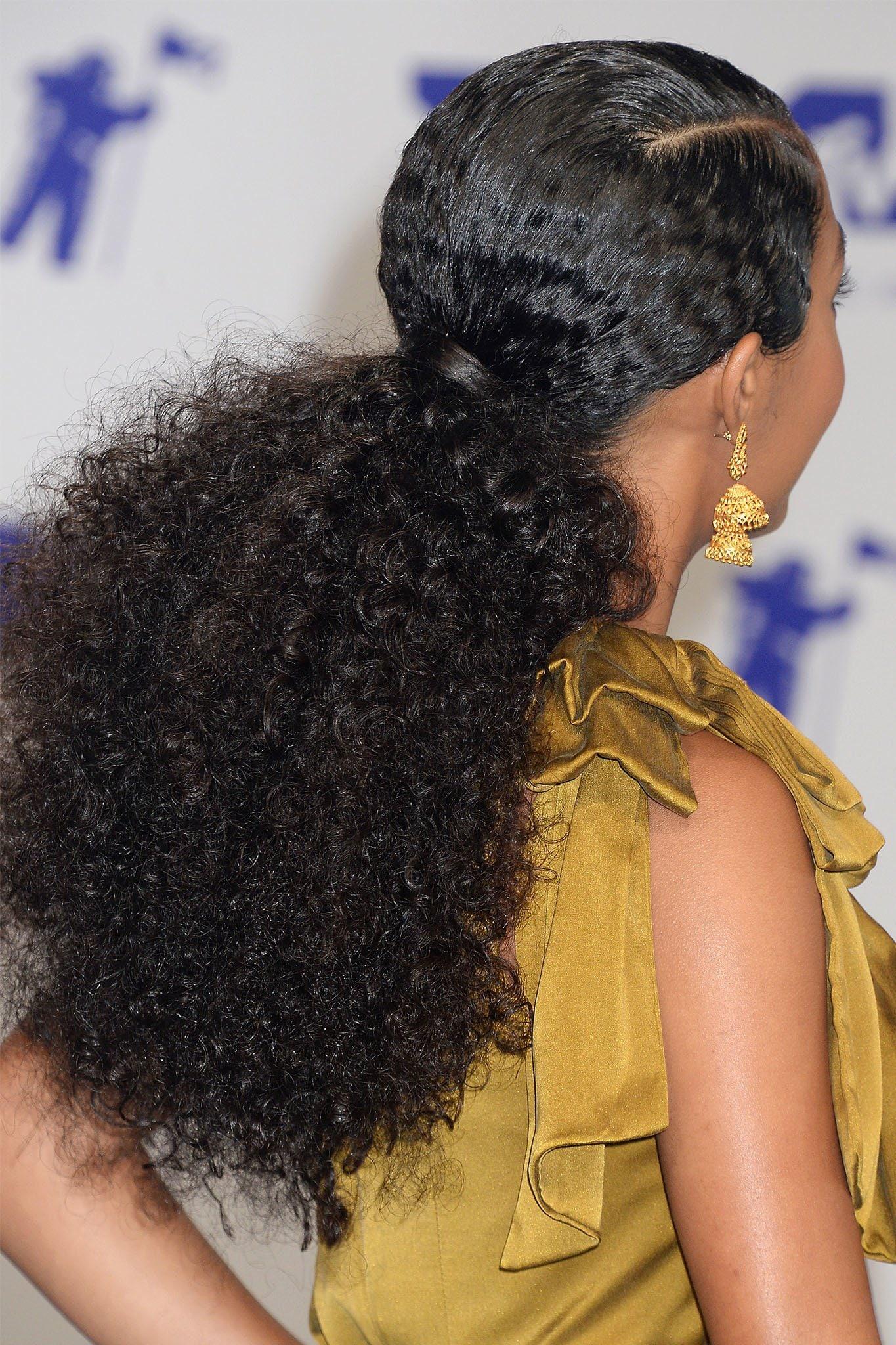 mujer de pelo negro con rulos con cola de caballo baja