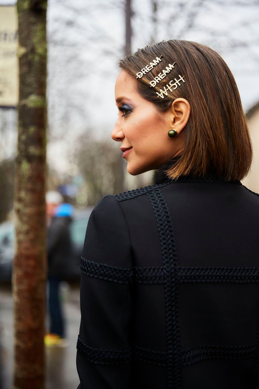 Mujer de pelo corto castaño con tres hebillas doradas en el pelo