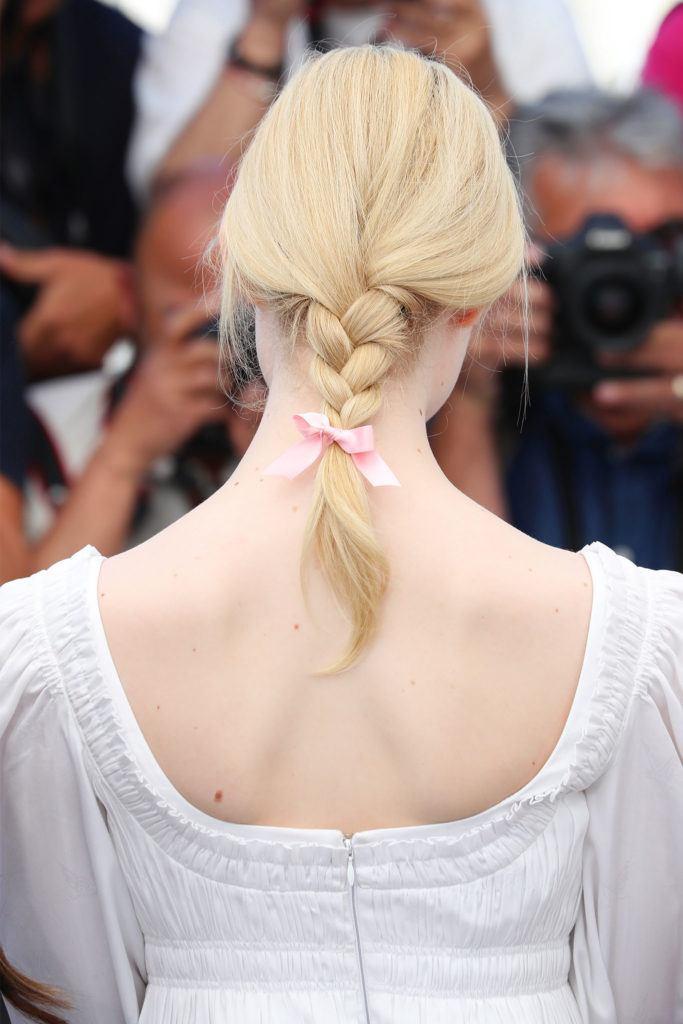 mujer de pelo corto rubio con trenza suelta sujetada con cinta rosa