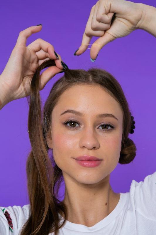 Chica de pelo castaño lacio seccionando su melena
