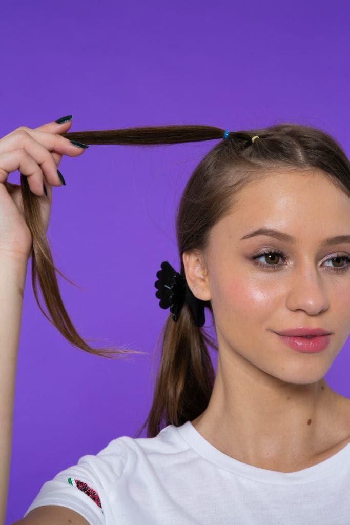 Chica de pelo castaño oscuro y lacio sosteniendo una colita