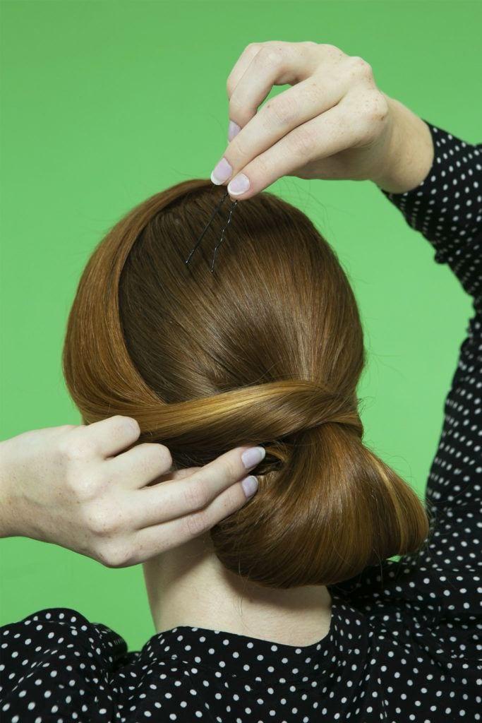 mujer sujetando con horquilla un peinado recogido