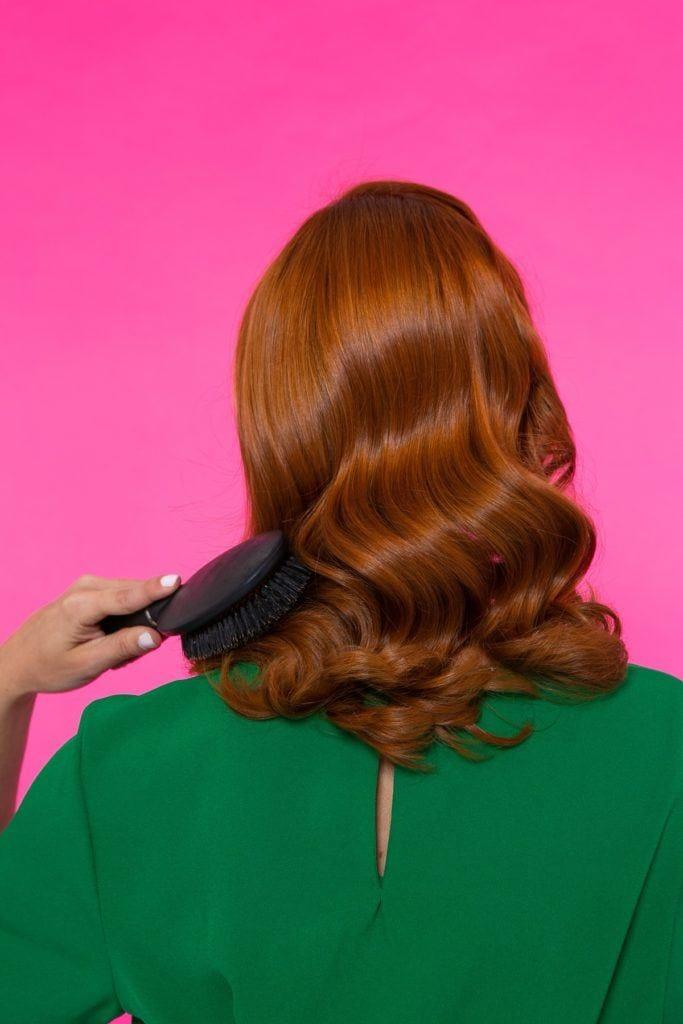 mujer de pelo rojo de espaldas peinando su pelo ondulado