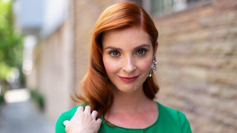 mujer de pelo rojo con ondas estilo hollywood con raya al costado