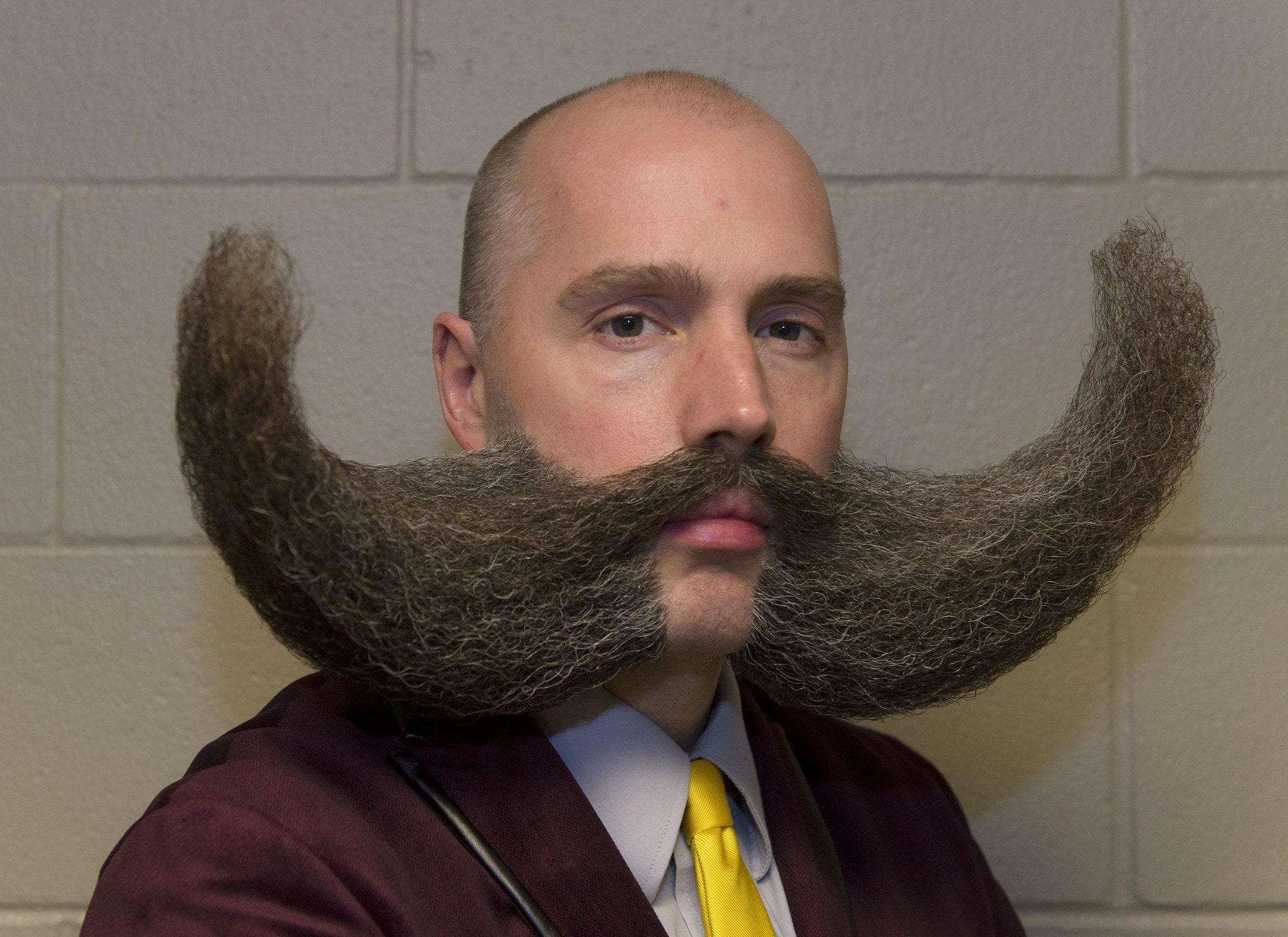 hombre calvo con bigote y barba extravagante