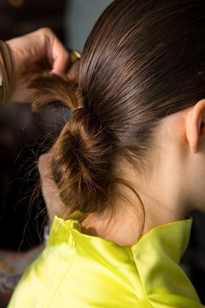 mujer con pelo castaño con rodete bajo
