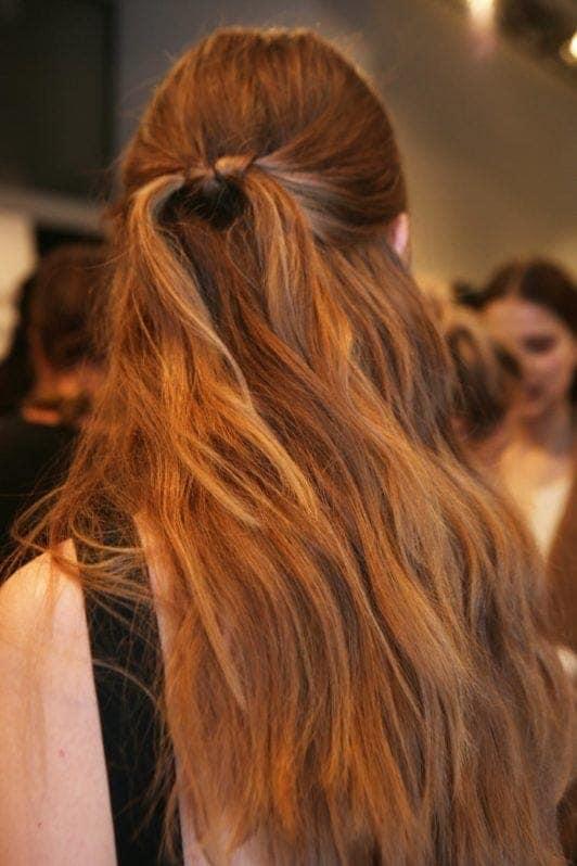 mujer de pelo castaño rojizo con reflejos rubios y cola con nudo