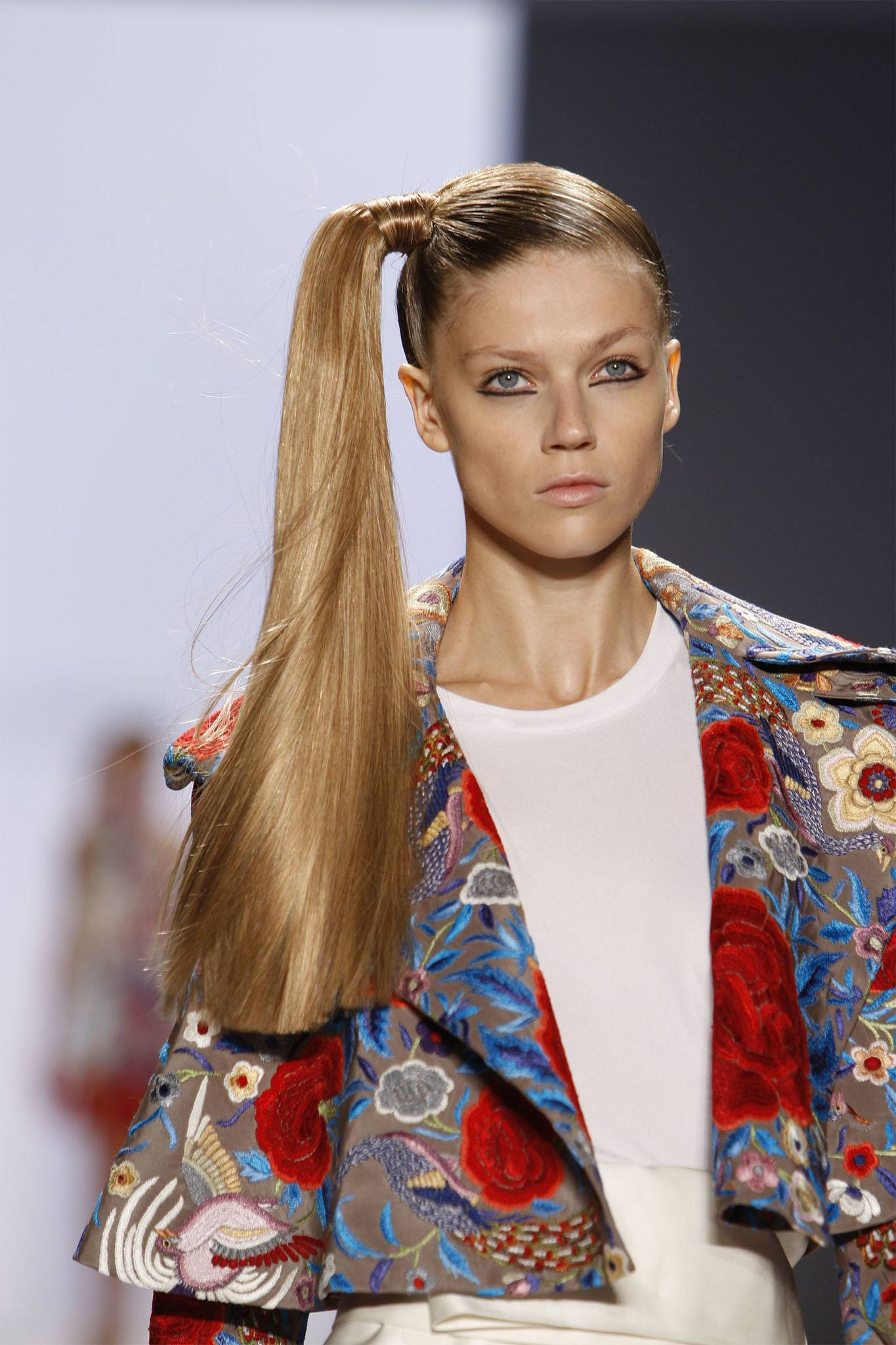 mujer de pelo largo rubio con cola de caballo de lado