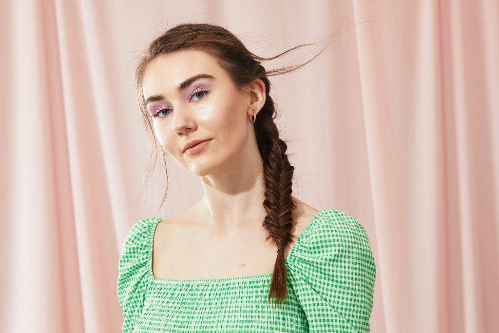 mujer de pelo largo con peinado al costado con trenza espiga