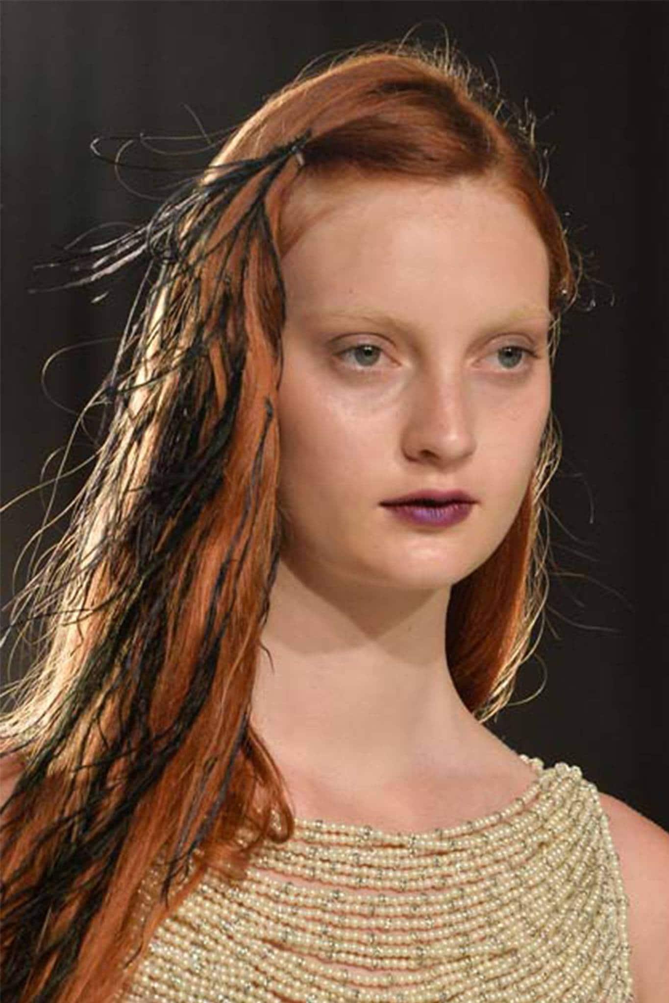 mujer pelirroja con peinado de lado con plumas