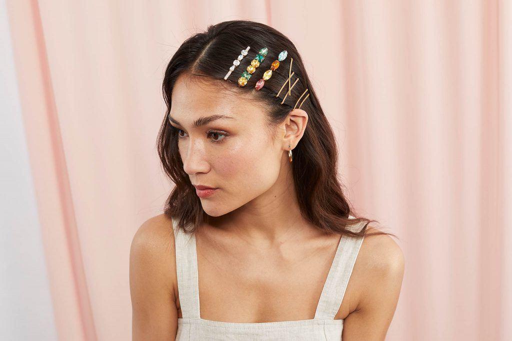 mujer asiática con pelo largo negro peinada con raya al medio y varias hebillas para el pelo de lado