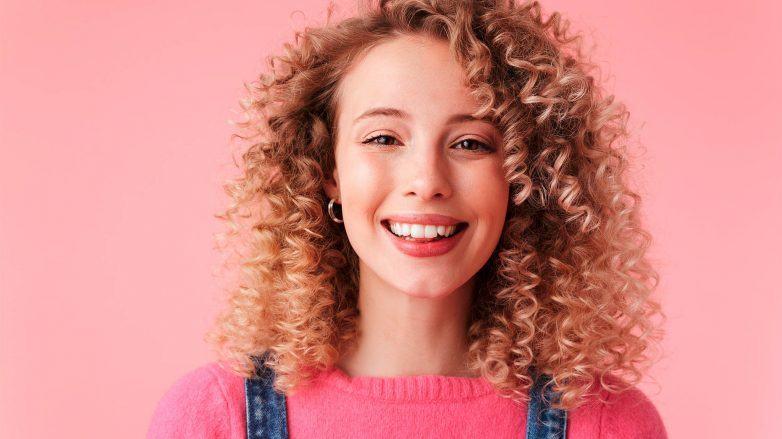 mujer sonriente con media melena rubia con rulos peinada con raya de costado, co wash