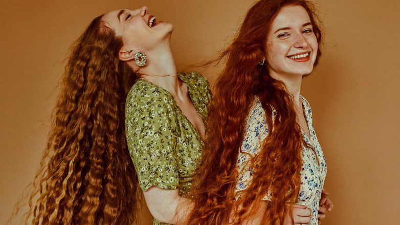 mujeres de pelo largo con ondas sonriendo, como hacer crecer el pelo rápido