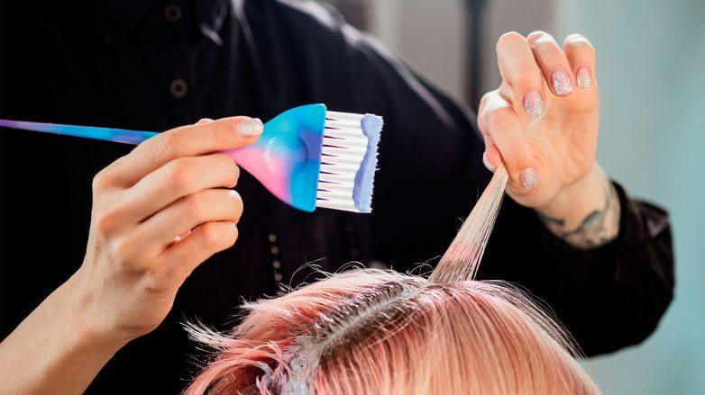 mujer con pincel aplicando tintura sin amoniaco sobre pelo claro