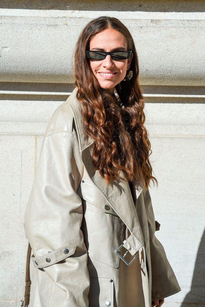 mujer de perfil al sol con anteojos y pelo largo suelto con rulos en las puntas y pelo color chocolate con mechas de pelo color caramelo