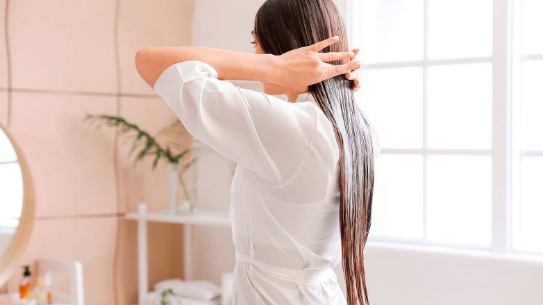 mujer de pelo largo lacio color castaño de espaldas aplicando aceite sobre el pelo, aceite de oliva para el pelo