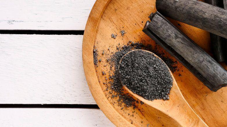 polvo de carbón activado sobre cuchara de madera, carbón activado para el pelo