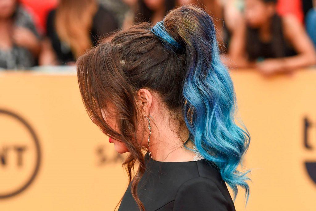 mujer de perfil con cola de caballo alta con ondas y puntas de pelo azul