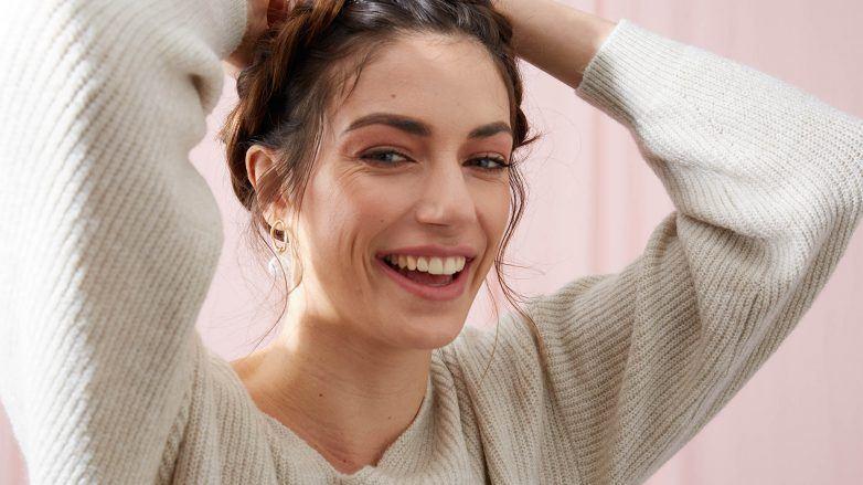 mujer sonriente con las manos en la cabeza, peinada con una trenza corona, la importancia de la higiene del cabello