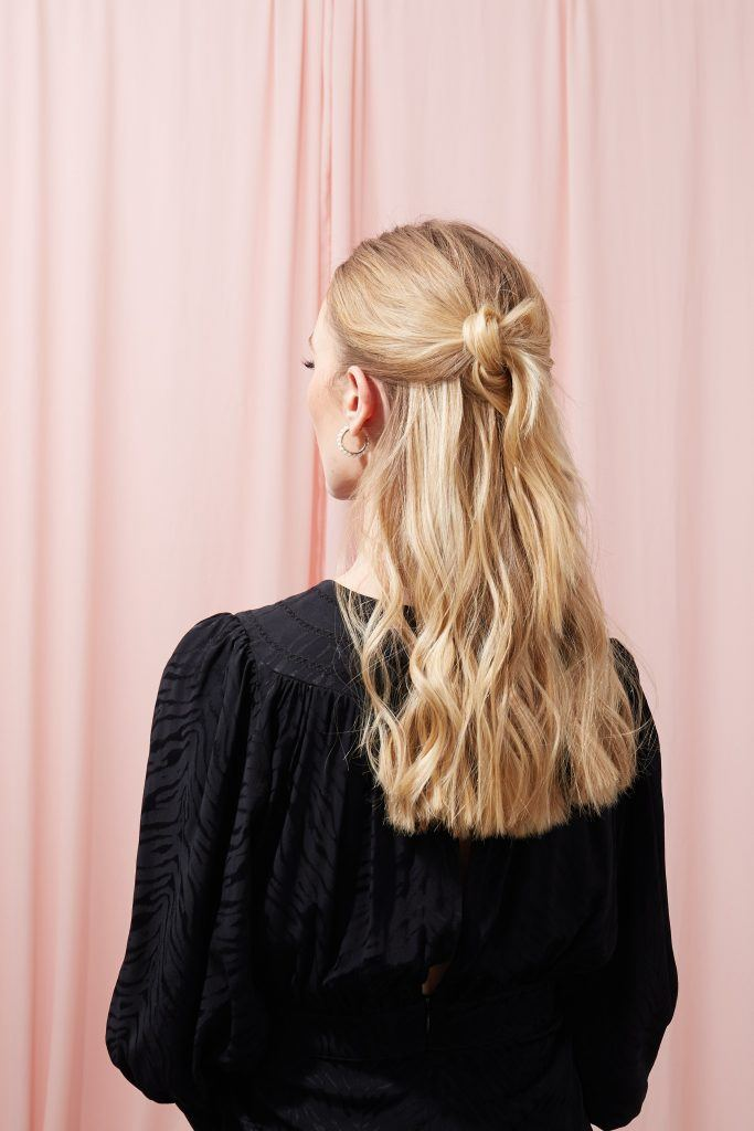 mujer de espaldas rubia de pelo largo son peinado semirecogido con nudo, peinados semirecogidos