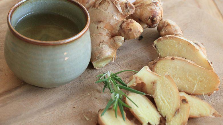 jengibre y romero sobre una tabla de madera y una taza, jengibre para el pelo