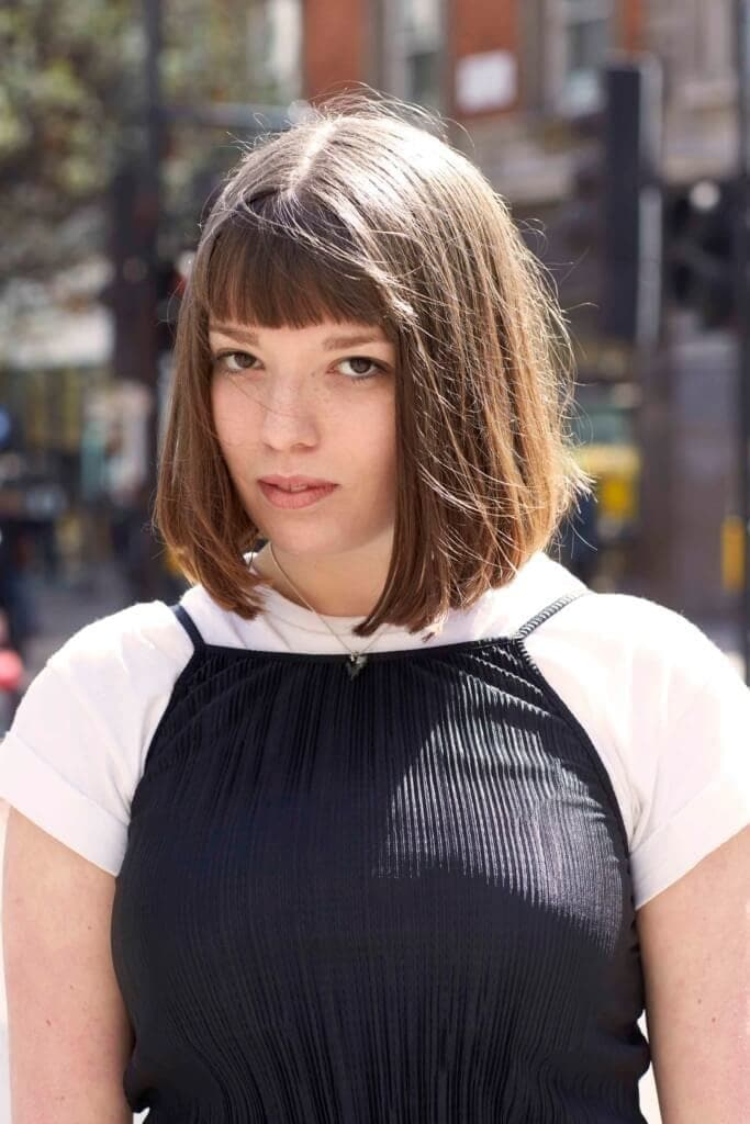 Short hairstyles for thick hair: Woman with medium brown shoulder length hair with rounded bangs. Woman is wearing a white t-shirt with a black cami top over the top.