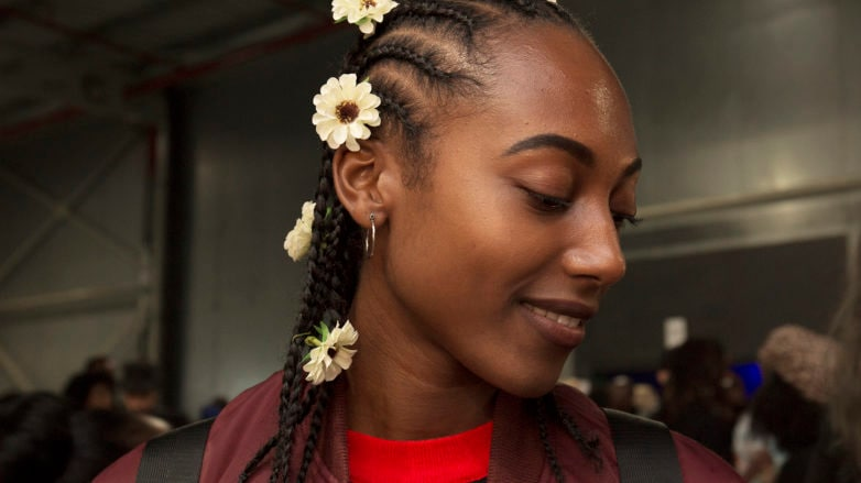 Cornrows: Woman at AfroPunk with hair in cornrow braids with sunflowers placed throughout her hair.