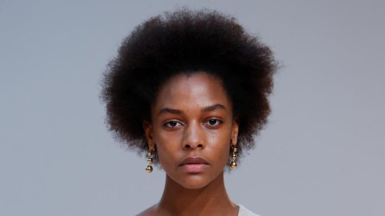 Deep conditioner for natural hair: Runway model with natural afro hair wearing a cream oversized dress on the Celine FW15 runway.