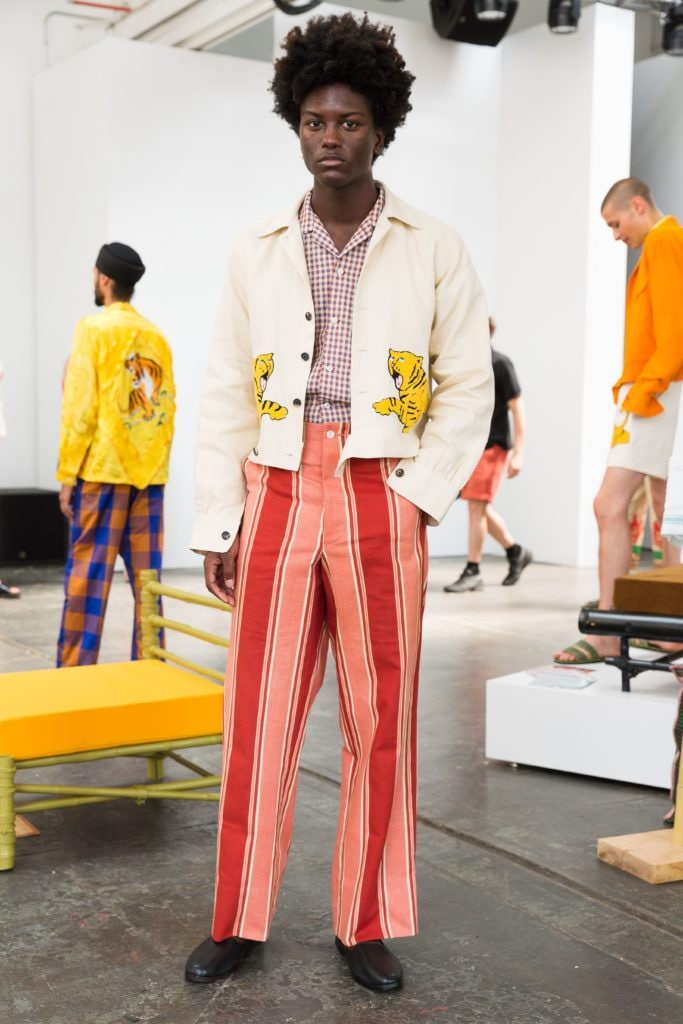 Men's hairstyles 2018: Model with natural large afro at men's fashion week presentation wearing 70s style outfit.