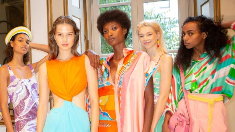 Shampoo: Five models backstage at Pucci SS19 show with different hair types and textures, from straight brown to short afro hair. All Models wearing bold coloured outfits.