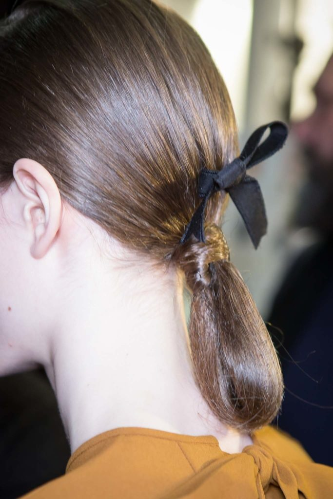 Hairstyles for long hair: Side back view of woman with light brown hair in a low twisted drop bun with a black ribbon seen in backstage image from Rochas FW17 show.