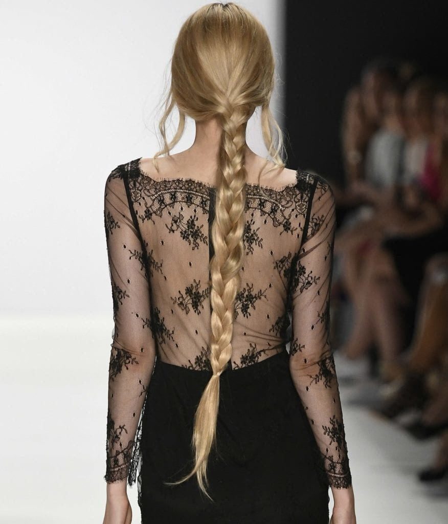 Hairstyles for thick hair: Back view of woman on the catwalk with very long bonde hair styled in a single braid. Model is wearing a lace detail top and black skirt